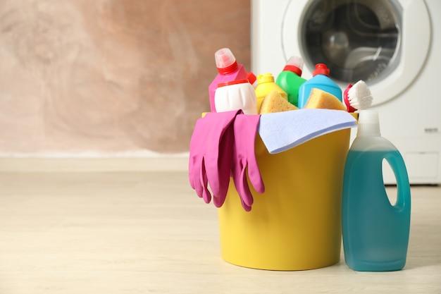 Emmer met wasmiddel en schoonmaakproducten op bruine achtergrond, kopie ruimte