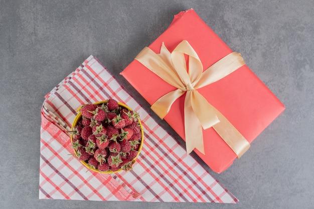 Emmer verse aardbeien en geschenkdoos op marmeren oppervlak. foto's van hoge kwaliteit