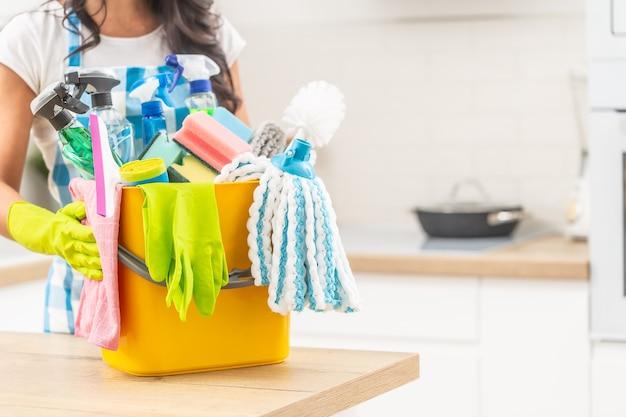 Emmer vol huisschoonmaakspullen op een keukenbureau met een vrouw die het in rubberen handschoenen vasthoudt.