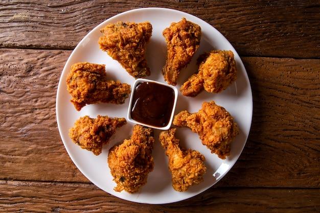 Emmer vol knapperige kentucky fried chicken met rook en barbecuesaus op bruine achtergrond. selectieve aandacht.