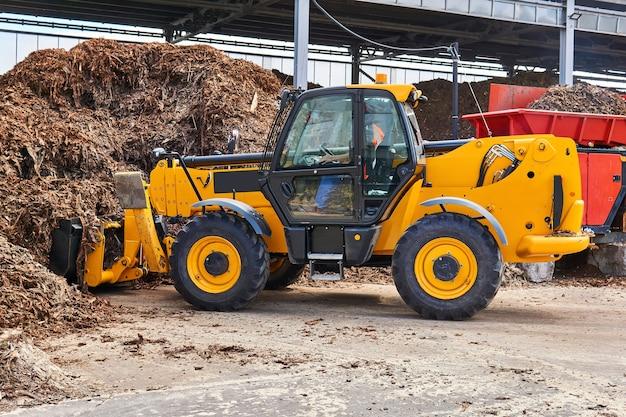 Emmerlader laadt houtschors in een industriële boomversnipperaar in een houtverwerkende industrie