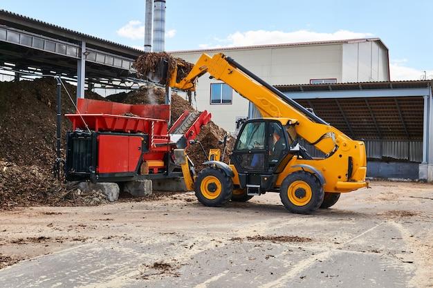Emmerlader laadt houtschors in een industriële houtversnipperaar in een houtverwerkende industrie