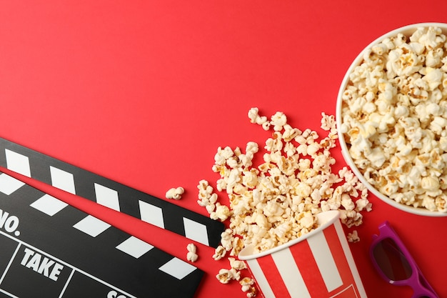 Emmers met popcorn, glazen en filmklapper op rode achtergrond