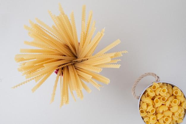 Emmers van gemengde rauwe pasta op wit.
