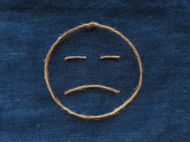 Emoji. droevige smiley gemaakt van touw op blauwe denim. detailopname