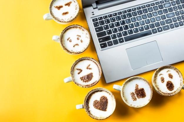 Emoji van de glimlach geschilderd op koppen van cappuccino naast laptop op een gele achtergrond