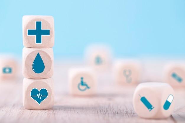 Emoticon pictogrammen gezondheidszorg medische symbool op houten blok, gezondheidszorg en medische verzekering concept