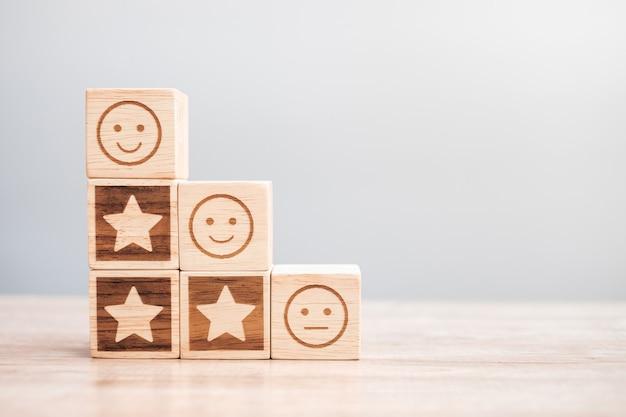 Emotie gezicht en ster symbool blokken op tabelachtergrond. servicebeoordeling, rangschikking, klantbeoordeling, tevredenheid, evaluatie en feedbackconcept