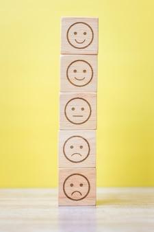 Emotie gezichtsblokken op gele achtergrond. servicebeoordeling, rangschikking, klantbeoordeling, tevredenheid, evaluatie en feedbackconcept