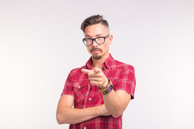 Emotie, mensen en gebaar concept - jonge knappe man wijst op je op wit oppervlak