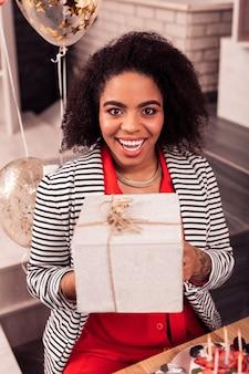Emotie van geluk. vrolijke gelukkige vrouw die naar je kijkt terwijl ze een cadeautje ontvangt