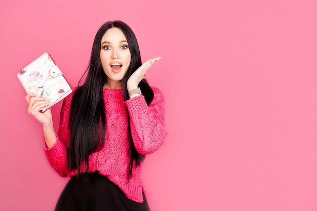 Emotie van sterke vreugde en verrassing in een vrouw met een notitieblok op een roze muur, met kopie ruimte. concept idee, vrouwenwerk, planning en zakenvrouw