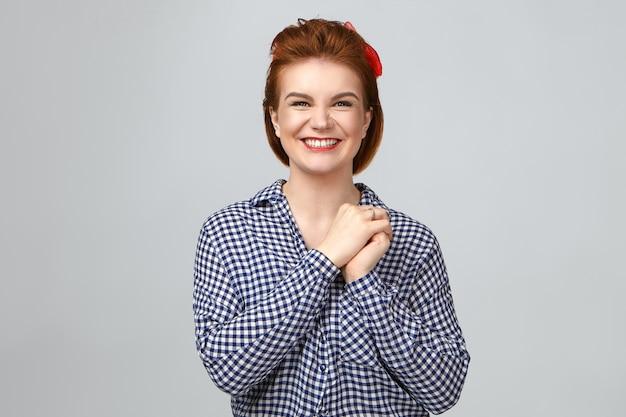 Emoties, gevoelens en reactie. studioportret van mooie jonge gember-toothy vrouw die gelukkig tevreden gelaatsuitdrukking maakt, breed glimlachend, verheugend terwijl ze goed positief nieuws ontvangt