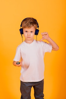 Emoties jongen luistert naar muziek met een koptelefoon op zijn telefoon, gele achtergrond. sprookjes voor kinderen in koptelefoons.