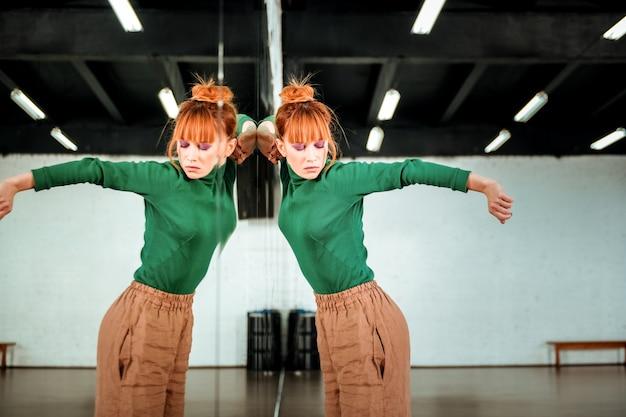 Emoties. leuke roodharige dansleraar die een groene coltrui draagt die emotioneel kijkt