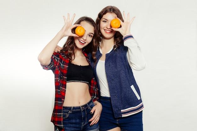 Emoties, levensstijl, mensen, tieners en vriendschap concept - twee jonge vrouw met verse citrusvruchten, sinaasappel en mandarijn en drinken uit een rietje op grijze achtergrond