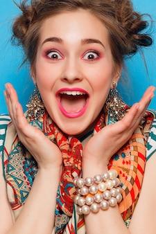 Emoties, mensen, schoonheid, mode en lifestyle concept - het portret van een jonge vrouw met geschokte gezichtsuitdrukking, over blauwe achtergrond