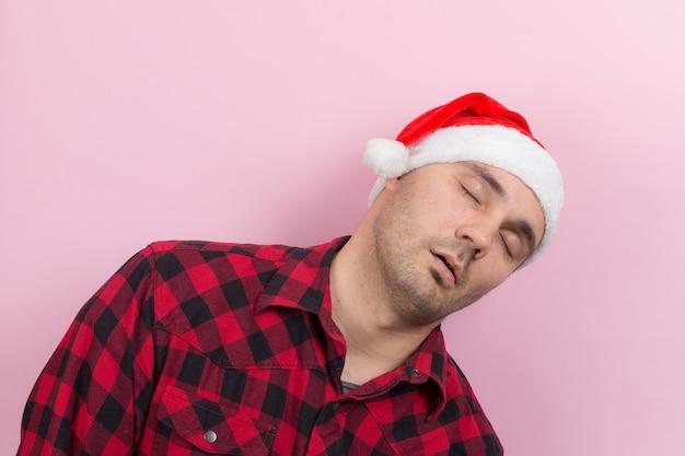 Emoties op het gezicht, moe, vakantie kater, bewustzijn. een man in een geruite konijn en een rode kerstmuts