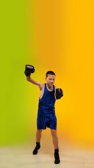 Emoties. tiener professionele bokser training in actie, beweging geïsoleerd op verloop achtergrond in neonlicht. schoppen, boksen. concept van sport, beweging, energie en dynamische, gezonde levensstijl.