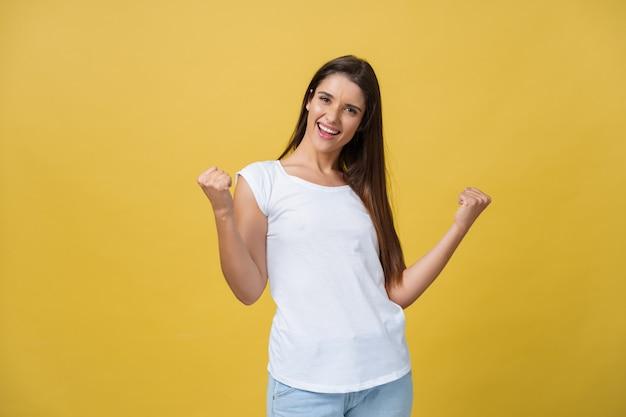 Emoties, uitdrukkingen, succes en mensenconcept - gelukkige jonge vrouw of tienermeisje die overwinning vieren die over gele achtergrond wordt geïsoleerd.