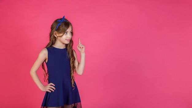 Emotioneel achtjarig tienermeisje laat zien dat er een idee is ontstaan, geïsoleerd tegen een roze achtergrond. kaukasisch kind in blauwe kleding en kapsel steekt zijn wijsvinger op. ruimte voor site kopiëren
