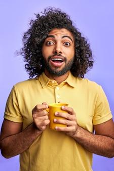 Emotioneel arabisch mannetje met mok in handen, die over purpere ruimte wordt geïsoleerd