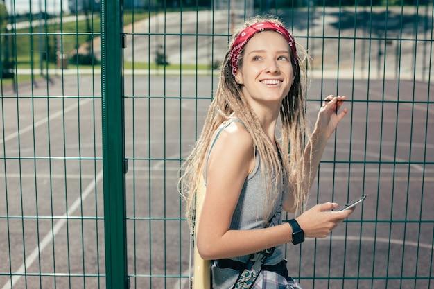 Emotioneel blij met dreadlocks die glimlachen en naar de lucht kijken terwijl ze bij het hek staan