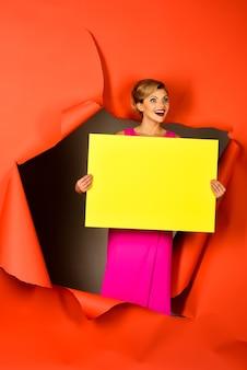 Emotioneel blond model met perfecte make-up rode lippen die rood papier breken verraste gelukkige vrouw