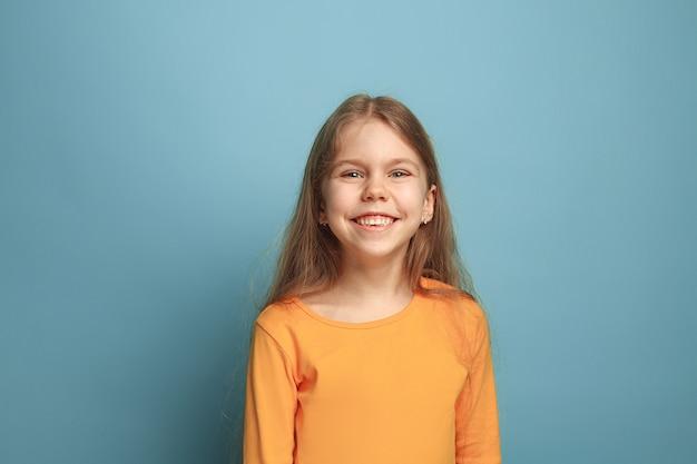 Emotioneel blond tienermeisje heeft een blije blik en een brede glimlach