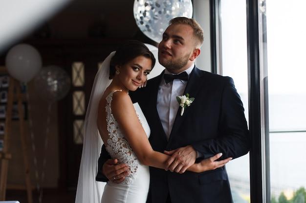 Emotioneel bruidspaar met ballonnen binnen