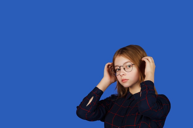 Emotioneel dertienjarig tienermeisje met een bril kijkt zorgvuldig naar een camera, geïsoleerd tegen een blauwe achtergrond. kaukasisch kind in zwarte kleding flirt met publiek. ruimte kopiëren