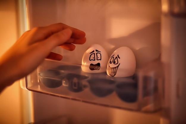 Emotioneel eieren. een vrouwelijke hand neemt een emotioneel ei uit de koelkast.
