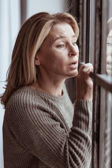 Emotioneel en verdrietig. volwassen vrouw met groene ogen die zich emotioneel en verdrietig voelt bij het raam