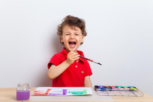 Emotioneel en vrolijk kind, een jongen, zit aan een tafel met verf en een penseel en tekent op een vel papier.