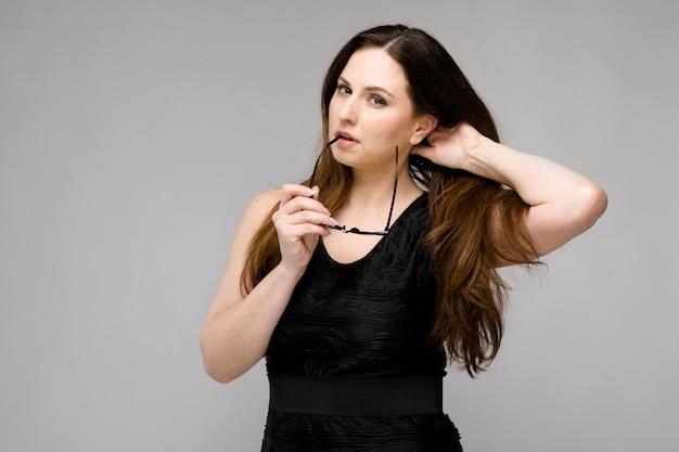 Emotioneel ernstig model dat zich in de glazen van de studioholding in haar haar van de handholding bevindt