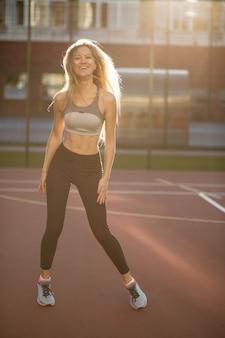Emotioneel fitnessmodel met perfect lichaam dat sportkleding draagt die op een tennisbaan in zonnestralen poseert