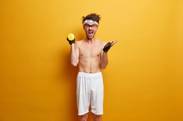 Emotioneel geïrriteerde man schreeuwt en heft halter op, streeft ernaar om voor de zomer wat spieren op te bouwen, gaat naar fitnessclub, gekleed in sportieve kleding, poseert tegen gele muur. gewichtheffen