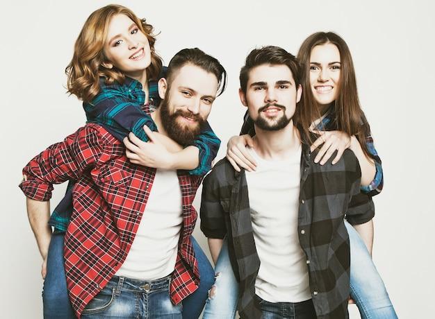 Emotioneel, geluk en mensen concept: groep jongeren die meeliften op witte achtergrond. speciale modieuze toning foto's.