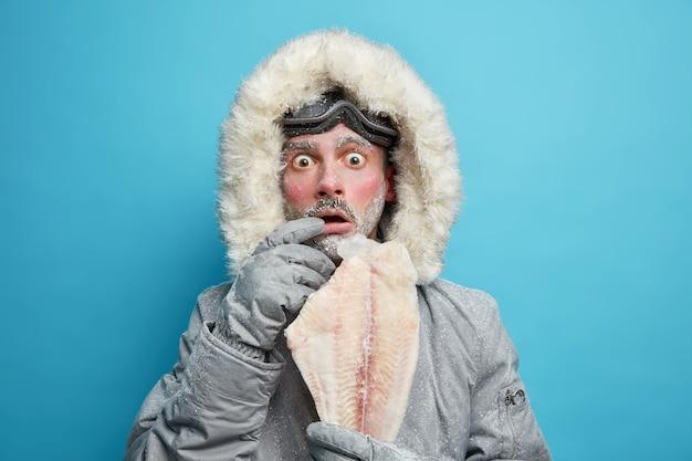 Emotioneel geschokte ijzige man gekleed in winterbovenkleding houdt bevroren vis vast die erg koud aanvoelt tijdens lage temperaturen op de noordelijke plaats.