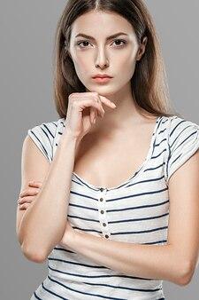 Emotioneel gezicht vrouw portret, mooie vrouw over grijze achtergrond poseren. studio opname.