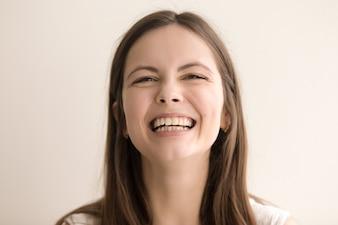 Emotioneel headshot portret van lachende jonge vrouw