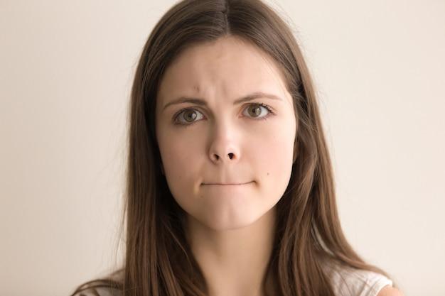 Emotioneel headshotportret van besluiteloze jonge vrouw