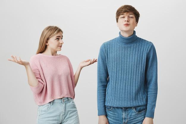 Emotioneel kaukasisch paar. jonge man gekleed in blauwe trui pruilt lippen, stuurt kussen