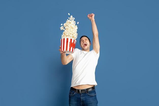 Emotioneel kijken naar bioscoop, vliegende popcorn. portret van de blanke jonge man op blauwe studio achtergrond. mannelijk model in casual stijl, pastelkleuren. concept van menselijke emoties, gezichtsuitdrukking