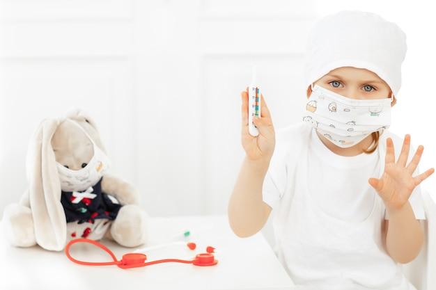 Emotioneel kind in medisch beschermend masker kijkt serios, termometr vasthoudend. kid spelen arts.