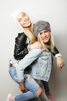 Emotioneel, levensstijl, geluk en mensenconcept: gelukkig meisje dat met vriendin meelift. studio-opname op witte achtergrond
