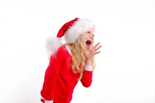 Emotioneel meisje in kerst kerstmuts staat met open mond en schreeuwen