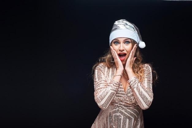 Emotioneel meisje in santa claus christmas-hoed op zwarte wordt geïsoleerd die