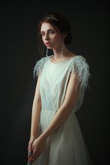 Emotioneel ouderwets portret van een vrouw in retrostijl in een licht transparante jurk met glanzende elementen op de schouders