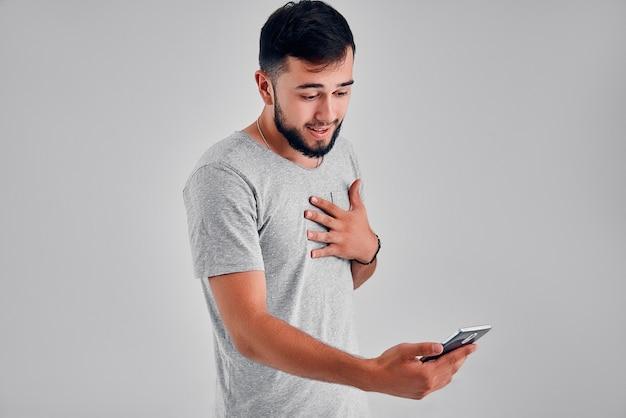 Emotioneel portret van baard hipster man schreeuwen terwijl hij op zijn mobiele telefoon over grijze achtergrond kijkt. zijn emoties losmaken.